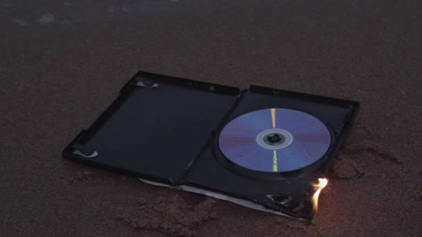 data cd disc in fire on the sand at coast