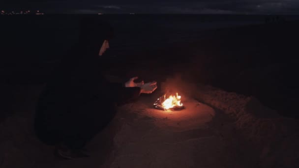 6317a324f941 Young man In black jacket seating near bonfire of burning shoes on sand at  coast– stock footage