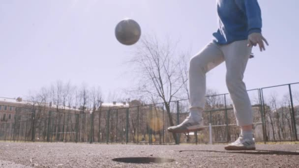 Football player dribbling and kicking ball. Soccer city park slow motion.