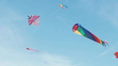 Many colourful kites in flight against blue sky and sunny day