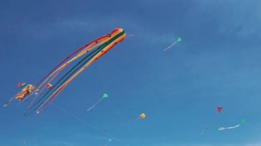 Kite with colorful stripes in form of octopus in flight. Blue sky and sunny day.