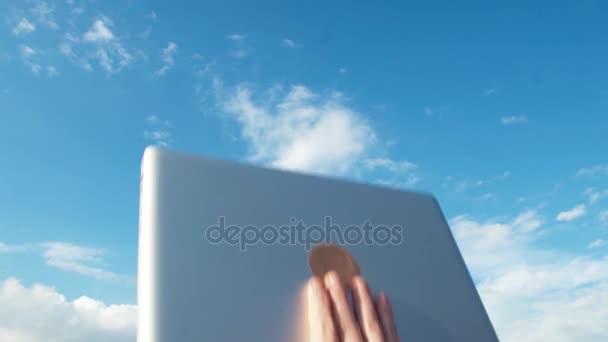 Male hand raise laptop up. Blue sky on background. Celebration success gesture