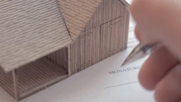 Mortgage contract sign. Model of the house and man confirming mortgage contract