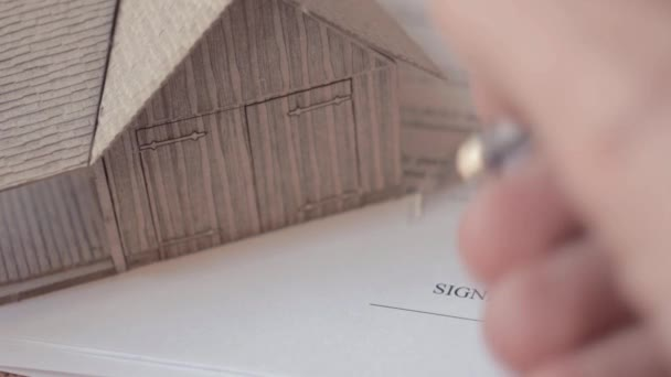 Male hand signing contract form in black ink. Model of buiding on contract page