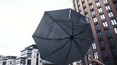 Male hand holding umbrella. The gust of wind pulls the umbrella out of hand