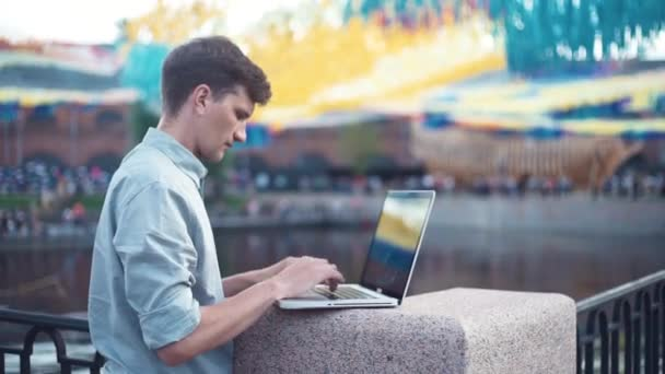 Kaukázusi, fiatal ember használ laptop állandó szabadban. Nyári napon
