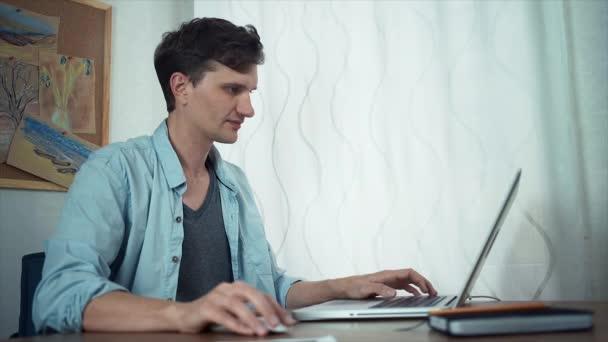 Chico guapo con portátil en la oficina. Tablero con dibujos de color ...