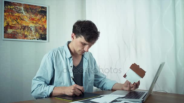 Freelancer designer sketching on tablet housing project using laptop