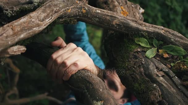 Young caucasian man climbs up top by slope clinging to the roots of trees