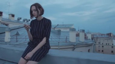 Young pretty woman using the smartphone sitting on the roof.