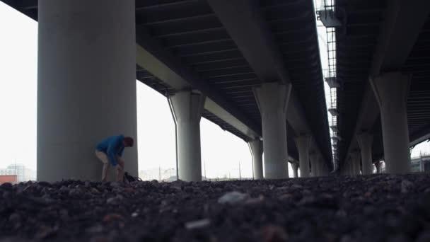 Mladý muž pomocí smartphone sedí na zemi pod silniční most
