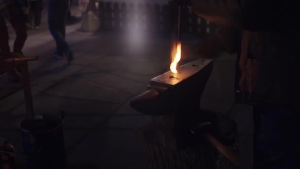 Schmiedemeister schmiedet abends im Freien heftige Metallhämmer. Heißes Eisen. Funkenflug.