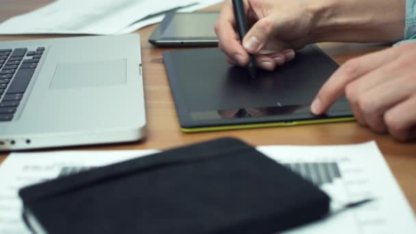 Designer working with graphics tablet, hands of man working with drawing tablet