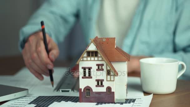Mužské ruky s tužkou. Architekt, vytváření projekt bydlení, model domu na stůl