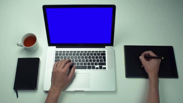Männliche Hände mit Grafiktab und Laptop mit grünem Bildschirm am weißen Schreibtisch