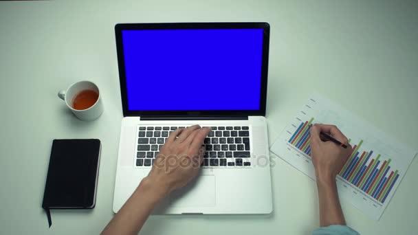 Pohled shora mužské ruce pracují s tištěnou grafy pomocí notebook s zelená obrazovka