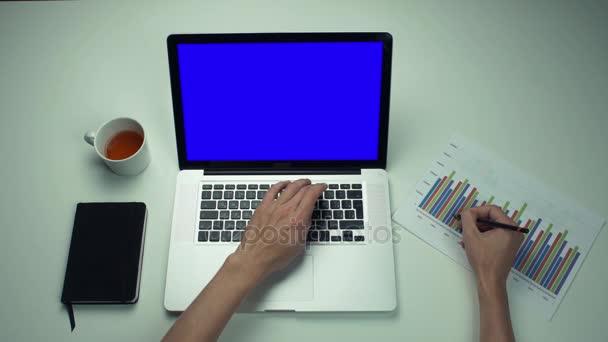 Männliche Hände arbeiten mit gedruckten Diagrammen am Laptop mit grünem Bildschirm