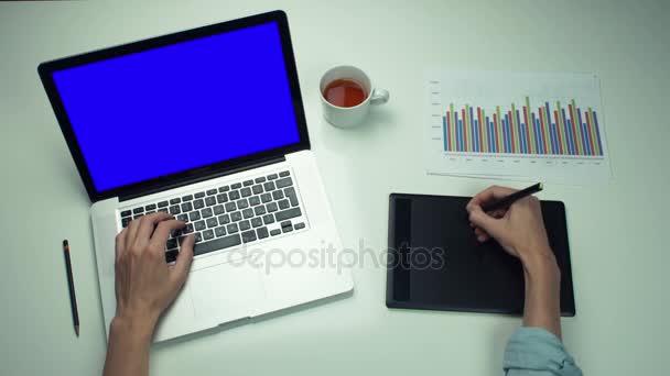 Felülnézet férfi kezét grafikai lap és laptop használata zöld képernyő fehér pult