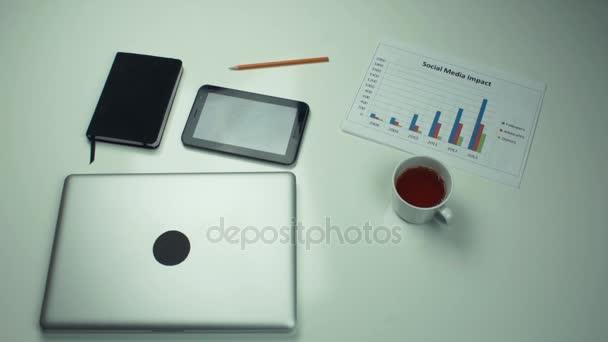 Felülnézet, íróasztal, irodai kellékek. Férfi kézi elhelyezés-ra iskolapad csésze tea.