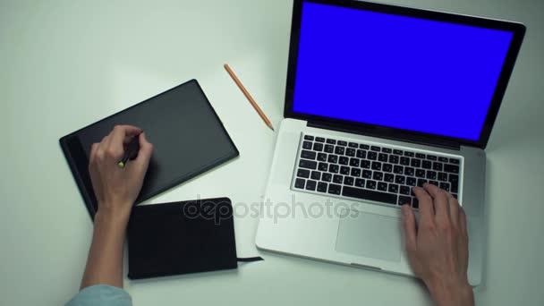 Felülnézet, íróasztal. Férfi leosztást használ digitális grafikus digitalizáló tábla