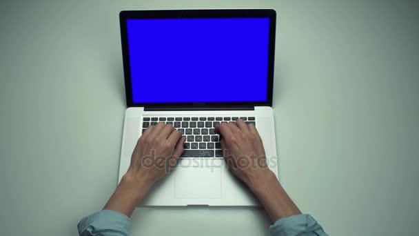 Pohled shora mužské ruce používat přenosný počítač s zelenou obrazovkou na bílý stůl