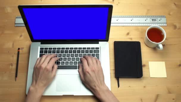 Felülnézet férfi kezében laptop használata zöld képernyő fából készült íróasztal