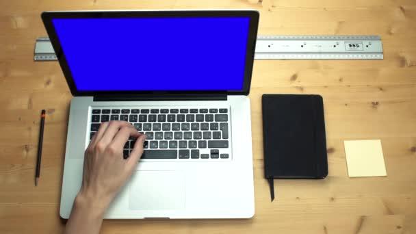 Männliche Hände mit Laptop mit grünem Bildschirm am Holztisch
