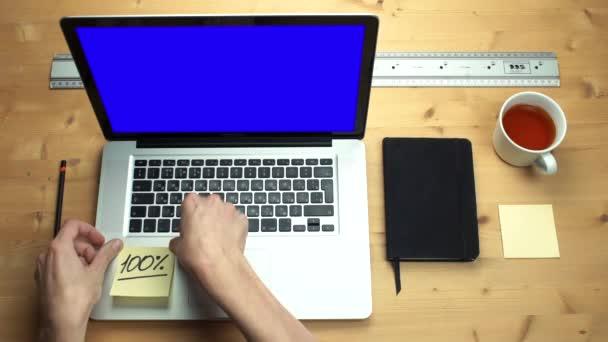 Felülnézet férfi kezét ragacsosság-ra laptop-val zöld képernyő öntapadó jegyzetek.