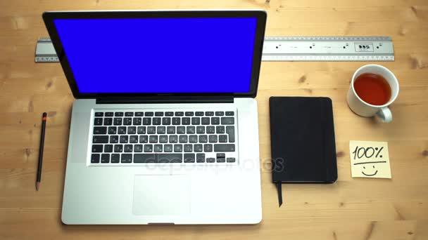junger Mann mit Laptop und grünem Bildschirm am Holztisch. Draufsicht auf Männerhände