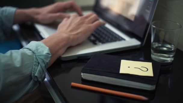 Üzleti ember használ a laptop otthon. Öntapadó jegyzet kérdés jel-ra iskolapad