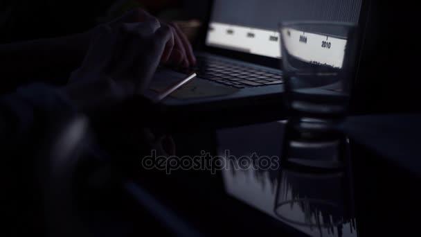 Mladý muž pomocí přenosného počítače v kuchyni v večer. Sklenice vody a tužka na stole