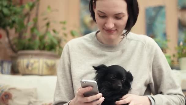 Fiatal lány használ smartphone ül a nappaliban aranyos fekete Csivava kutyával