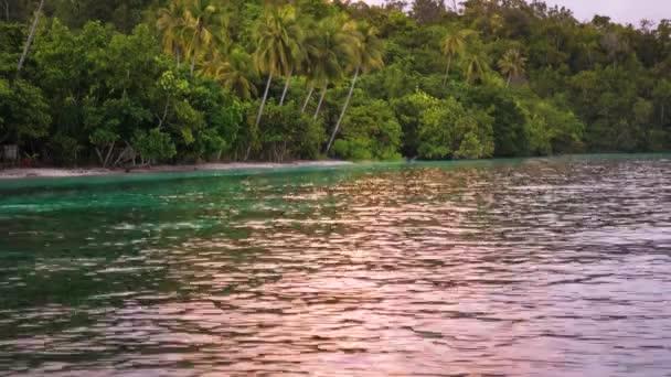 Západ slunce světlo odrážející na vodní hladině v blízkosti homestay chatek na pláži, Gam ostrov, Raja Ampat, Západní Papua, Indonésie
