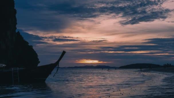 Longtail boats parked near beautiful Phra Nang Beach during sunset
