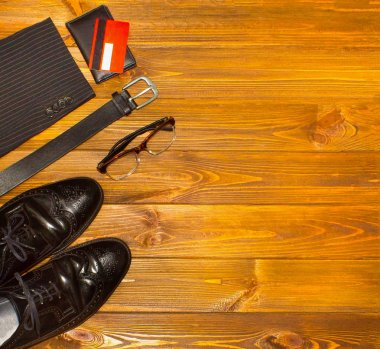 The elegant male set: mens shoes, leather belt, on the wooden background.