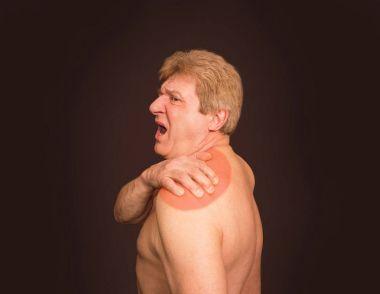 Close-up of senior shirtless man with shoulder pain over black background