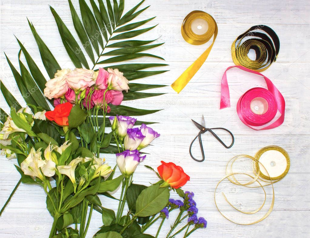The florist desktop with working tools on white wooden background