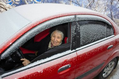 Active senior woman - smiling retired lady driving car