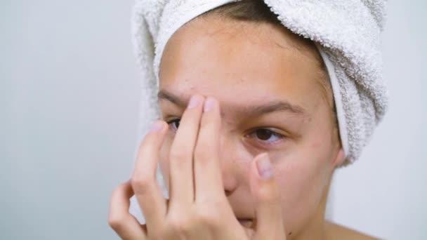 Teenage dívka v koupeli ručník dotýkající se obličeje mají kožní problémy