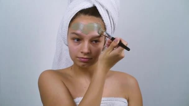 Teenagermädchen mit Akne in Badetücher gewickelt, Tonmaske auf Gesicht auftragen