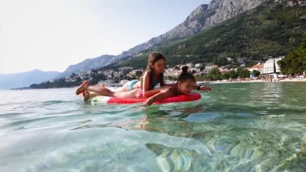 Happy girls swimming on inflatable mattress in shallow waters of blue sea