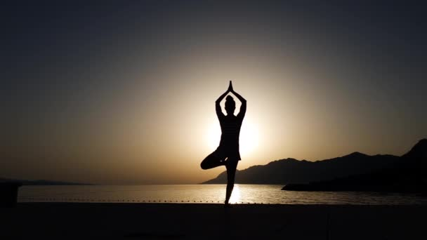 Silhouette of girl balancing in yoga asana at sunset by the sea