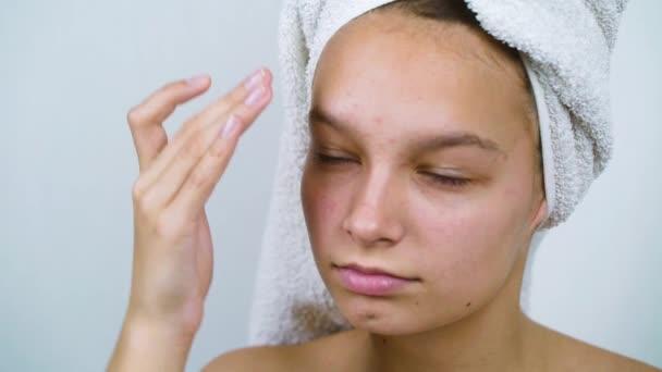 Teenager-Mädchen untersucht ihr Gesicht mit Akne nach dem Bad
