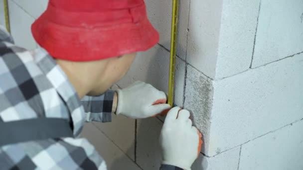 Junge Bauarbeiter in Arbeitskleidung befestigen Befestigungsklammern und Metallschiene an Blockwand