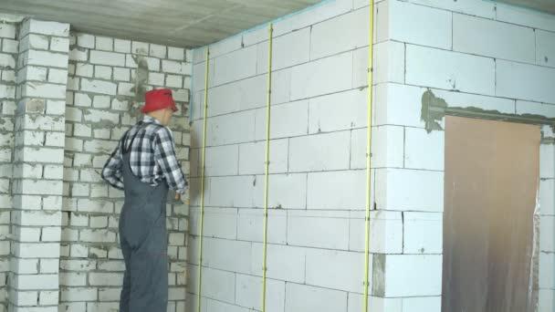 Junger Bauarbeiter montiert Metallschienen an Porenbeton-Blockwand