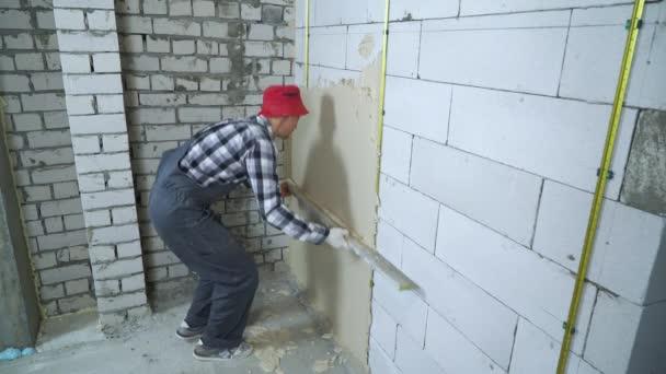 Szakmai builder szintező vakolat a blokk falán segítségével vonalzó