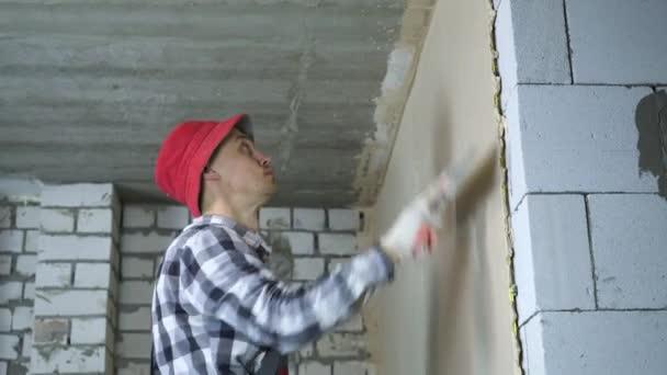 Junger Bauarbeiter ebnet verputzte Wand an Hausbaustelle