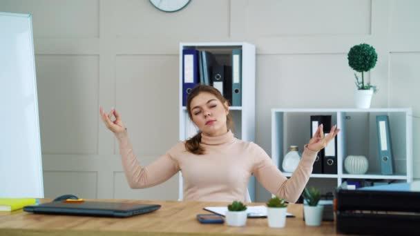 Female entrepreneur meditating in yoga posture at workplace
