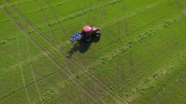 aerial top down shot of red tractor riding on green agricultural field