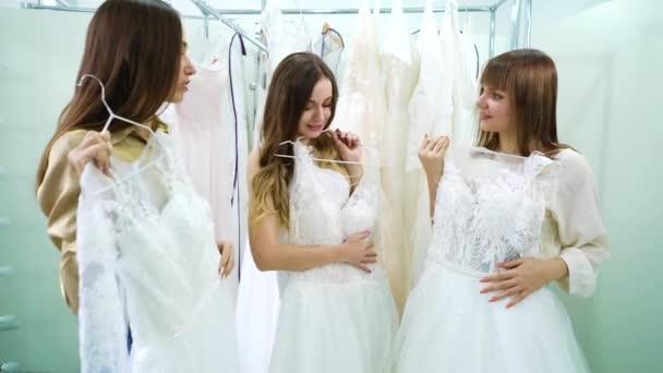 Csinos lányok esküvői szalonban próbálgatják a ruhákat és beszélgetnek.